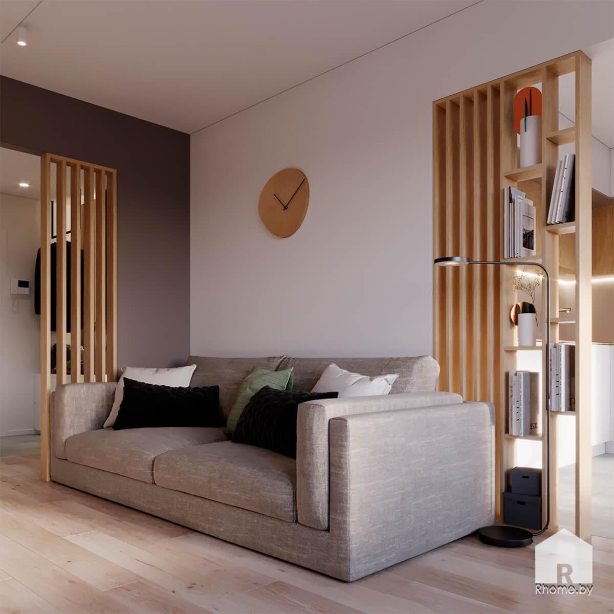 Квартира в Новой Боровой. Серый диван в светлой гостиной рядом с деревянным стеллажом