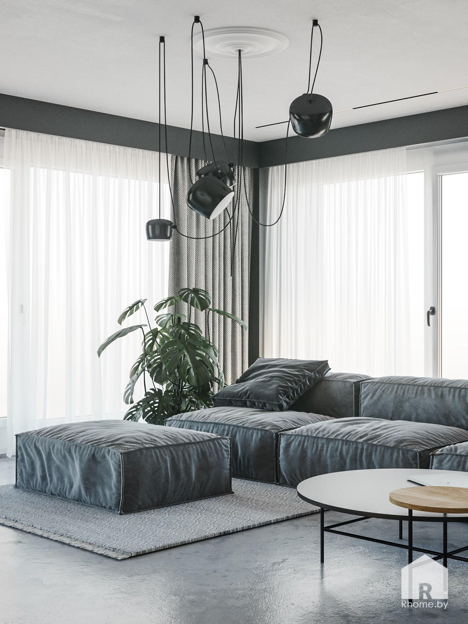 Мягкий серый диван в гостиной с большими окнами и черной люстрой над ним и круглым журнальным столиком рядом.