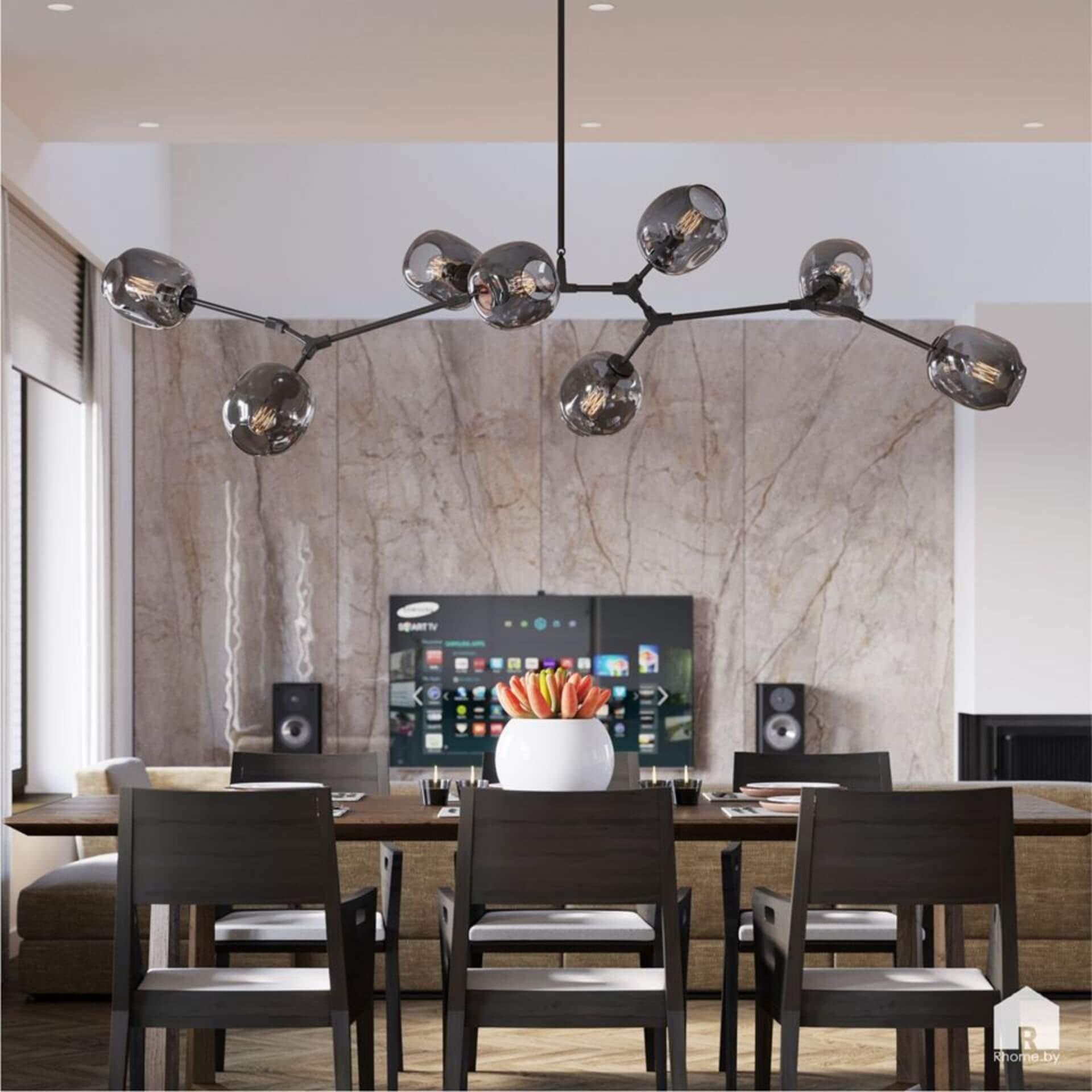 Столовая с большим светильником над столом. Телевизор на зданем плане на фоне серой стены.