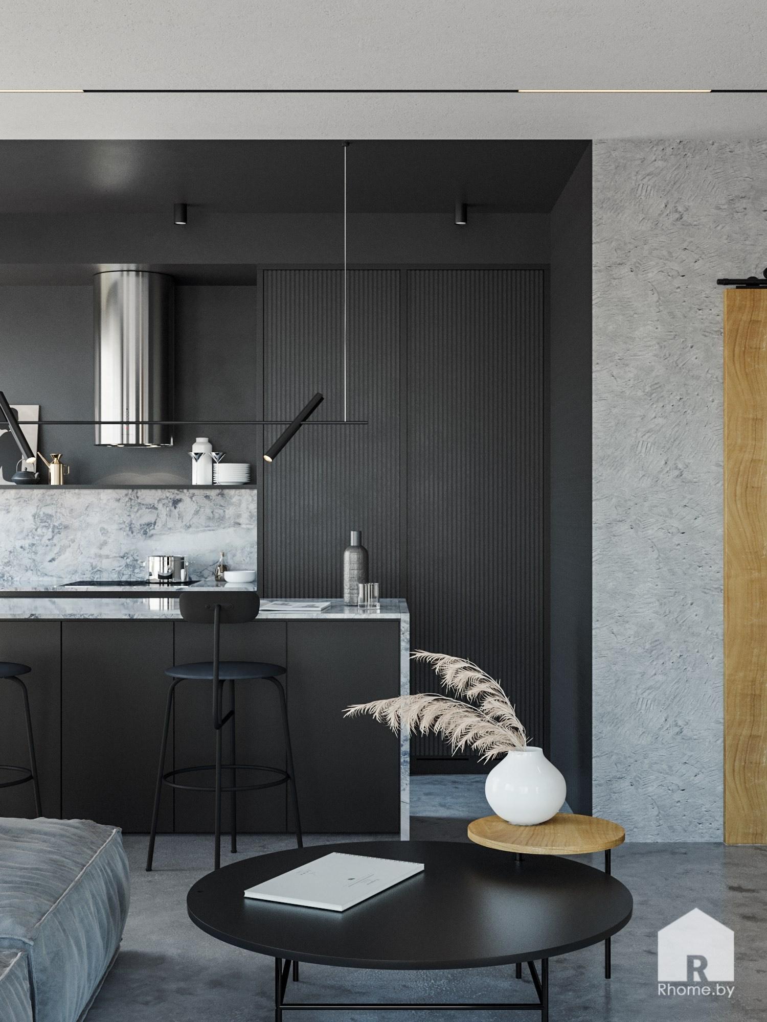 Черная кухня на заднем плане, а на переднем –Мягкий серый диван в гостиной с большими окнами и черной люстрой над ним и круглым журнальным столиком рядом.