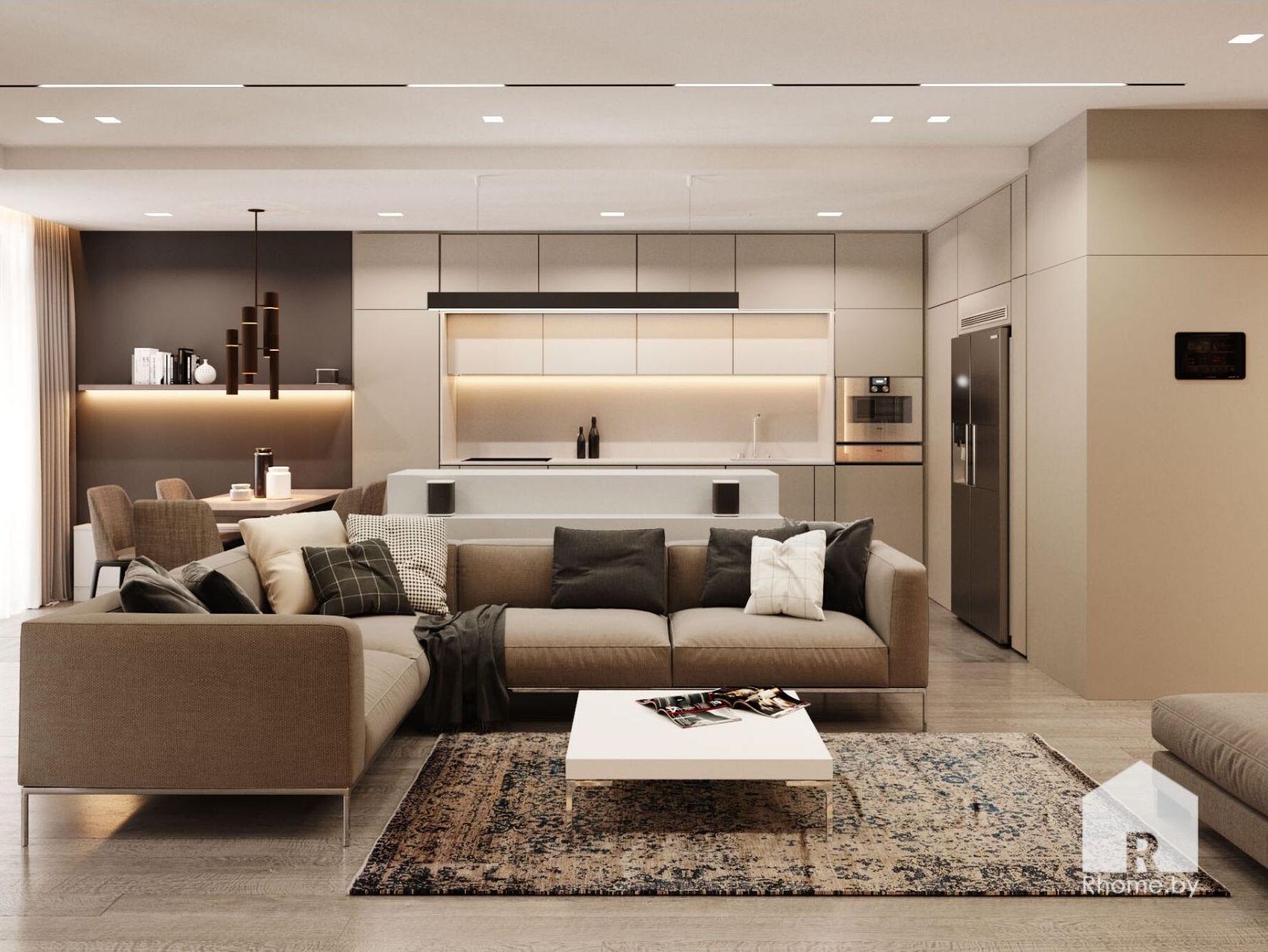 Гостиная с большим коричневым диваном, низкий журнальный столик стоит на ковре, а на заднем плане белая минималистичная кухня.