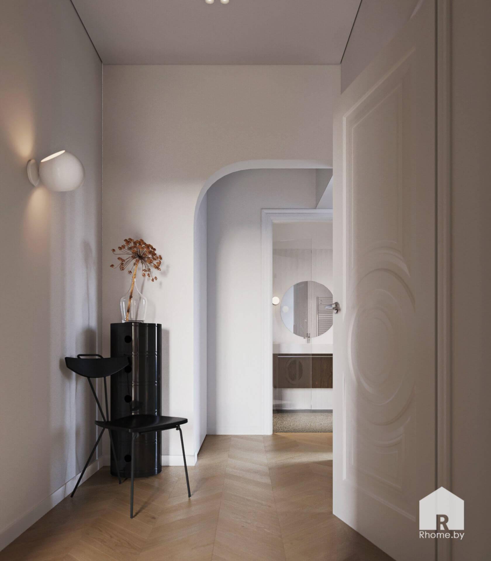 Светлый холл с черной тумбой, минималистичным светильником на стене, черной тумбой в углу и круглым зеркалом на дальней стене. Белыйе двери и арочный портал.